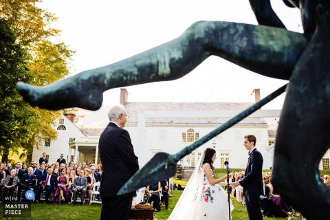 Wedding photography from the Southern Vermont Arts Center — The bride and groom are framed by a sculpture during their ceremony
