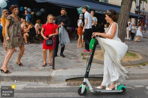 paris wedding photographer — bride arriving at reception venue on electric scooter rental