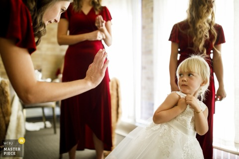 Our Lady of Lourdes Catholic Church, Denver, CO wedding photographer — The flower girl reacts when a bridesmaid prompts her for a high-five while getting ready for the wedding.