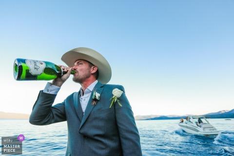 加利福尼亚州南太浩湖的婚礼摄影师-仪式结束后,新郎在太浩湖中部的一条船上只喝了一小口香槟。