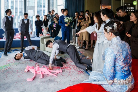 Beijing China wedding day game photography at the Hotel bridal room | In receiving relatives, the best man does the same action as the pink leopard doll at the request of the bridesmaid.