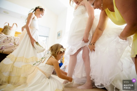 South Lake Tahoe wedding photographer | The bride gets help with her shoes from her flower girls and maid of honor.