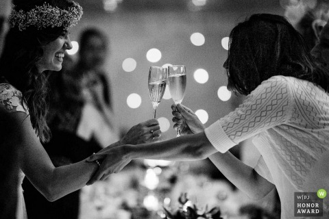 Photo: Bride and her mum doing a cheers 'clink' during the speeches at Chippenham Park wedding venue