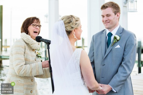 Wedding photo from Martell's Water's Edge, New Jersey officiant bride and groom laugh during ceremony
