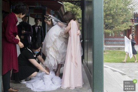 Beijing China Bride getting into her dress - Asia wedding photo