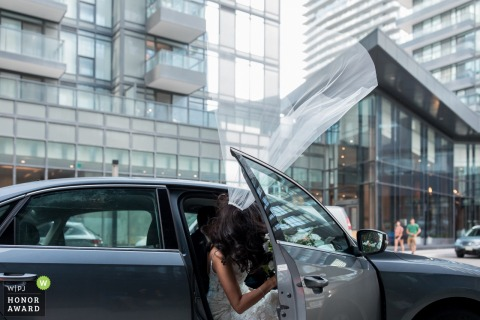 Ontario Bride Leaving Home Photo | Toronto wind takes her veil up as she gets into the car.
