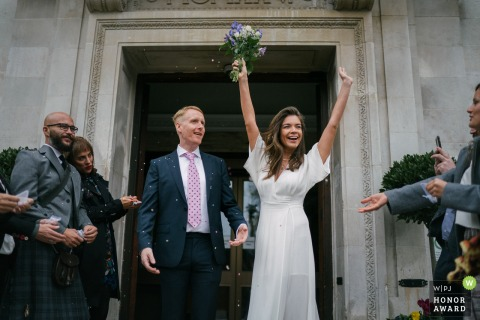 Islington Town Hall wedding photo: Bride celebrating after her wedding
