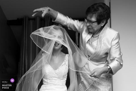 巴黎婚礼摄影师:新娘的母亲正在帮助她的面纱