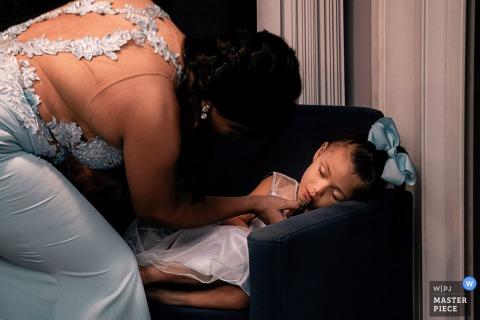Brasilien Make Up / Friseursalon Hochzeitsbilder | Brautjungfer, die ihr Kind für die Zeremonie fertig macht, während sie schläft