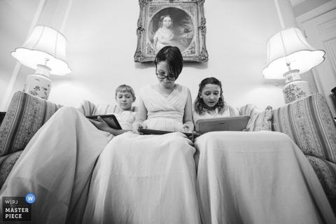 华盛顿特区的惠特莫尔之家婚礼场地照片| 初级伴娘花时间,等待仪式开始,而母亲则帮助新娘调整礼服。