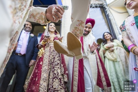 Sikh Association of Baltimore, Randallstown, MD wedding photographer -  Retrieves shoes, as the tender exchanges hands, following a brisk negotiation after the ceremony.