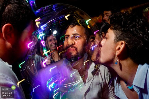 Fethiye, Turkey - Help Beach Club wedding venue photo: guests having fun with a transparent ballon at after party