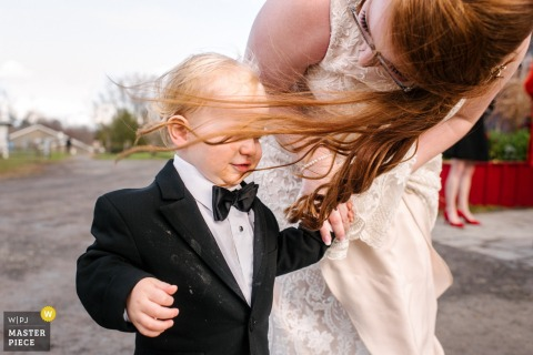 Photography from outside Strathmere Lodge reception venue, Ottawa - Photo of the bride's hair into her toddler's face