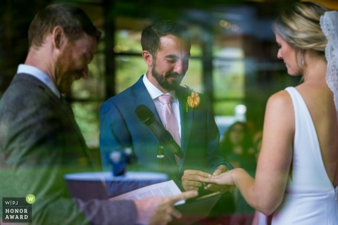 Vail Golf Club Wedding Venue Photo: Groom putting on ring with reflection of golf course.