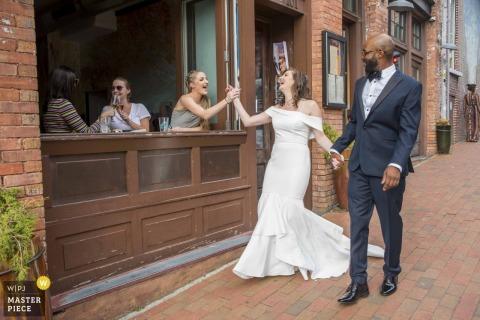 Asheville, North Carolina High Five für die Braut, als sie mit ihrem Bräutigam die Straße entlang geht - Wedding Day Photography