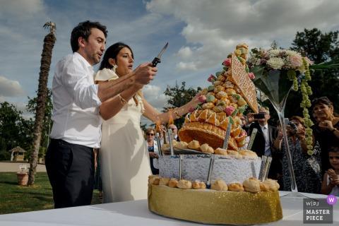 Chateau de la Garrigue, Francia fotografía de boda del corte de pastel al aire libre