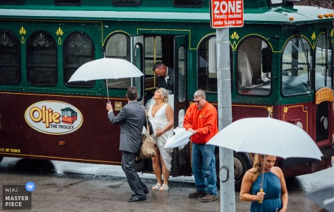 NebraskaCeremony Photography - The Bride getting off of trolley looking up at it raining - Ollie The Trolley