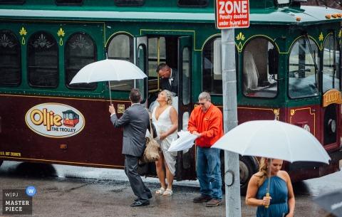 Photographie de cérémonie au Nebraska - La mariée descendant du chariot en train de regarder la pluie - Ollie The Trolley