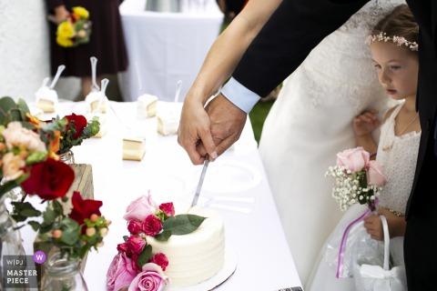 Hinterhof-Hochzeitsfotograf Los Angeles Kalifornien - Bild eines Blumenmädchens, das herein während des Kuchenausschnitts späht