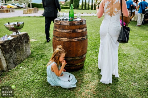 Vinska fontana Marezige wedding venue photo of a young Girl eating in the shade behind the barrel.