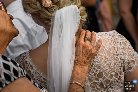 Photography at the wedding party- a grandmother gives a hand to the bride