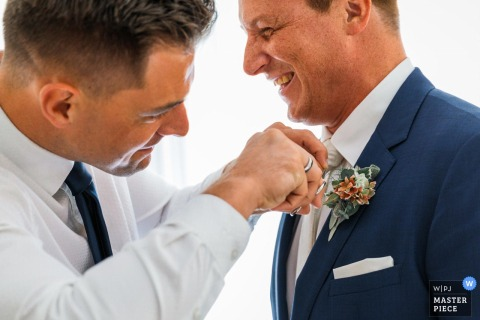 Germanygetting ready pictures - the best man cuts the flowers from his groom