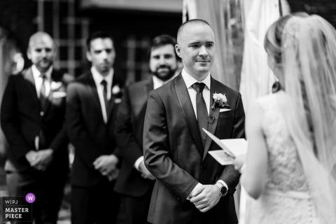 Fotógrafo de la ceremonia de boda de NJ: el novio derrama una lágrima mientras la novia lee sus votos y los padrinos de boda observan.