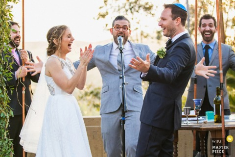 De Brandeis-Bardin Campus van de Amerikaanse Joodse Universiteit, Brandeis, Californië Het pas getrouwde stel viert met hun rabbijn en familie onder de joodse chuppah.