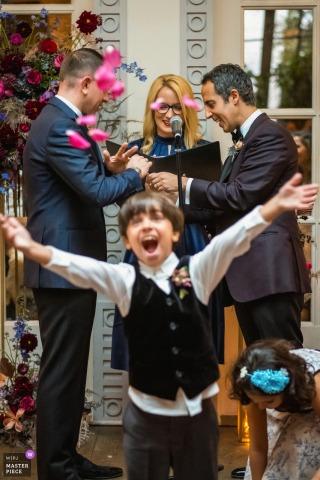Spago, Beverly Hills, Kalifornien Hochzeitsfotografie | Der Ringbär und der Sohn eines Paares werfen abrupt Rosenblätter, um zu feiern, während sie während ihrer Hochzeitszeremonie die Ringe tauschen.