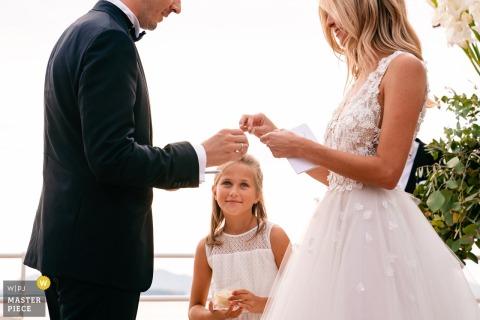 Fotos de la ceremonia de boda de Bélgica: una niña mira con admiración cuando la novia está a punto de ponerse el anillo