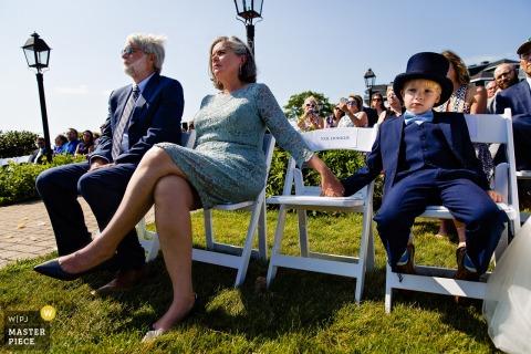 French's Point, photographie de mariage à Stockton Springs dans le Maine - Un porteur de bague et les parents de la mariée regardent la cérémonie du mariage