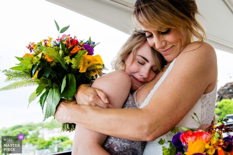Camden, Maine wedding photography | A bride hugs her daughter after her wedding ceremony