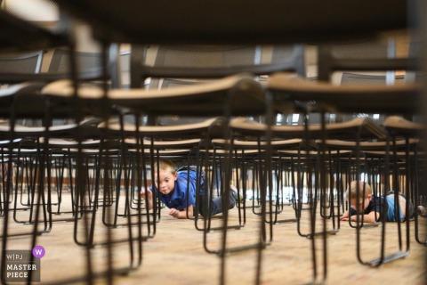 Los niños se suben debajo de las sillas en un Fargo North Dakota - Fotoperiodismo de boda