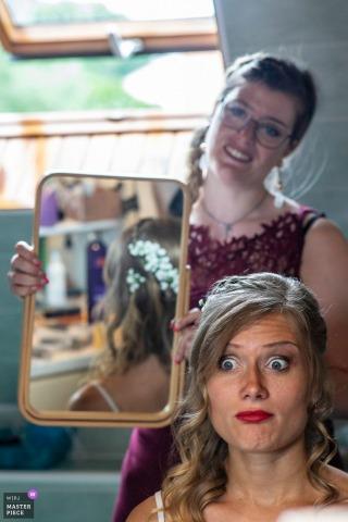 Lièpvre se prépare pour la photographie de mariage - La mariée vérifie ses cheveux dans un miroir vertical.