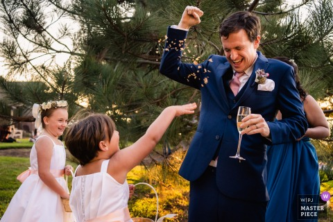 The wedding flower girls throw their remaining flowers at the groom - Del Mar, Ca wedding photography