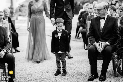 Auvergne-Rhône-Alpes wedding ceremony pictures of an unhappy little ring bearer walking down the aisle.