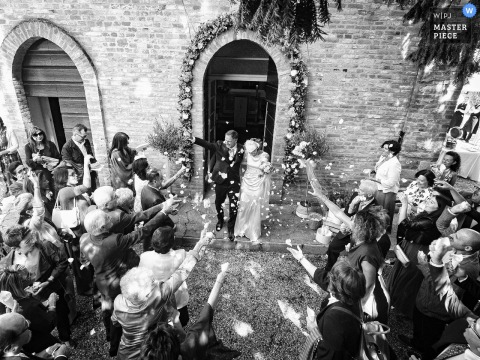 Villa Castello Torrazzetta, Borgo Priolo, Italy - Photography of guests throwing rice at the bride and groom after the wedding ceremony