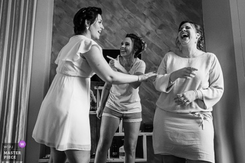 Bastide des Hirondelles fotografía del día de la boda de las novias y la dama de honor divirtiéndose durante las preparaciones