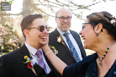 Photo du lieu de la cérémonie à l'extérieur de l'Ontario: la mère du marié lui touche la joue avec amour