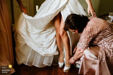 Wedding images from venue Château Tourreau - bride getting help with her shoes