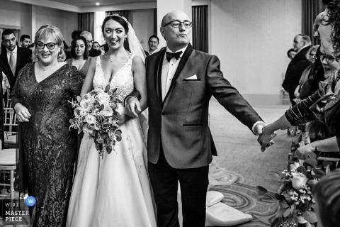 Le père de la mariée tend la main vers l'invité alors qu'il promène la mariée dans l'allée du cérémonie de mariage à Edgewood Country Club, New Jersey