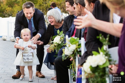 Ceremony Photography of Kids: Flower girl gets guided by grandmothers at the start and end of aisle during Martell's Water's Edge New Jersey wedding ceremony