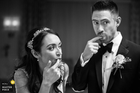 Bride and groom simultaneously lick cake off their fingers while making surprised reactions at Edgewood Country Club NJ wedding