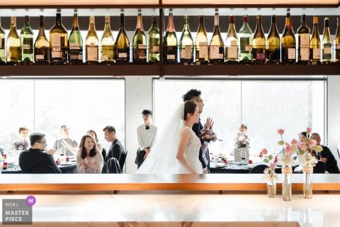 Photographie de mariage de Taipei à Taïwan montrant les mariés entrant dans le bar de la réception.