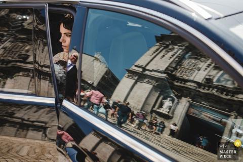 menino conhece menina - portugalska fotografia ślubna przedstawiająca pannę młodą wysiadającą z samochodu z odbiciami kościoła w szybach samochodowych