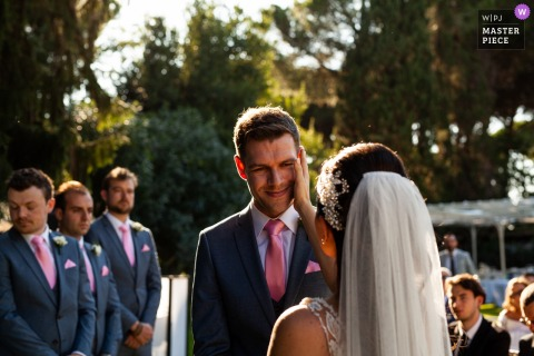 Villa Trebzia - Rome Italy / ceremony photography as the bride wipes a tear from the groom during the ceremony