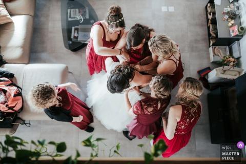 Onnen, photographie de mariage en Suisse montrant la mariée Préparez-vous dans cette image aérienne avec des demoiselles d'honneur en robe rouge