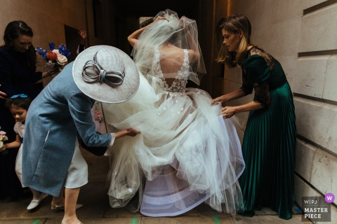 St Bride's Church, London wedding pictures | Bridesmaid adjusting the bride's dress