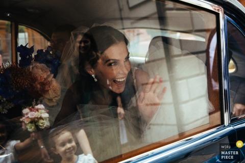 St Bride's Church, London Hochzeitsfotografie - Die Braut winkt dem Blumenmädchen zu, als sie zur Zeremonie kommt