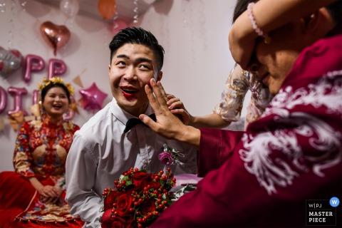 Photos de mariage Chengdu Sichuan | Assis sur le lit est le frère de l'époux. La soeur de la mariée couvre les yeux de l'époux. Le marié prépare du rouge à lèvres pour son frère. En ce moment, l'expression de son frère est très intéressante
